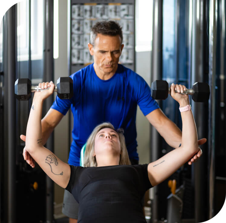 A fitness trainer spotting a woman who is lifting weights