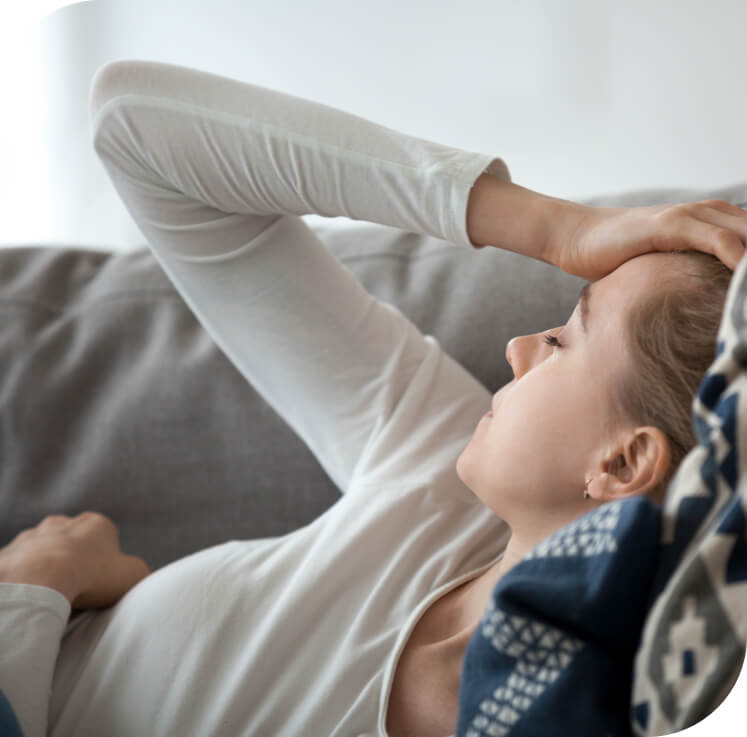 Young woman with head ache lying on couch