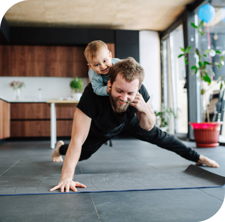 Man completing fitness activities with his son on his back